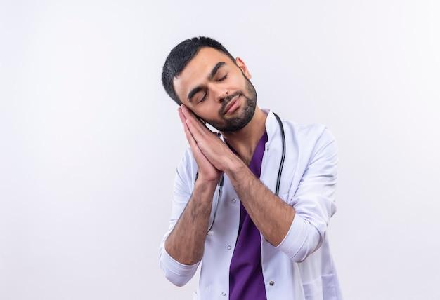 Avec les yeux fermés jeune médecin de sexe masculin portant une robe médicale stéthoscope montrant le geste de sommeil sur blanc isolé