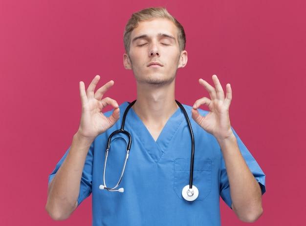 Avec les yeux fermés jeune médecin de sexe masculin portant l'uniforme de médecin avec stéthoscope montrant le geste de méditation isolé sur un mur rose