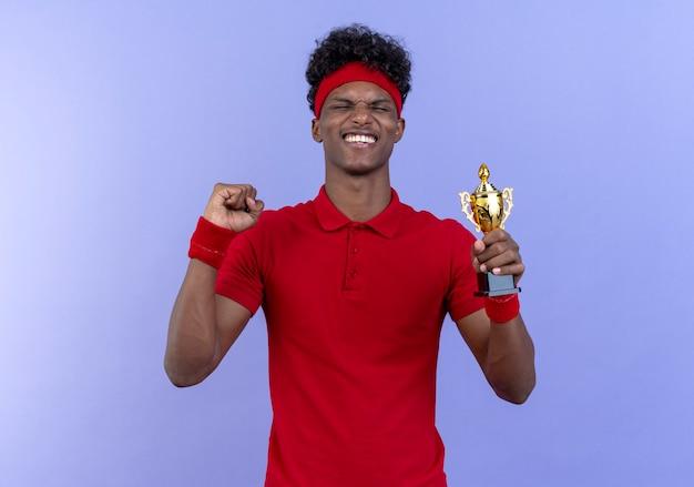 Avec les yeux fermés joyeux jeune homme sportif afro-américain portant bandeau et bracelet tenant la coupe du gagnant et montrant oui geste isolé sur bleu