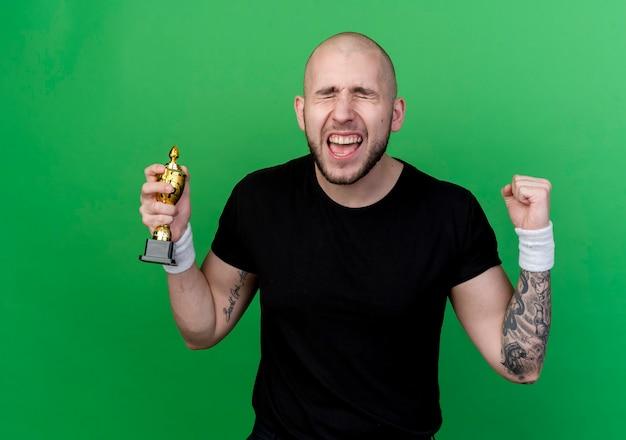 Avec les yeux fermés joyeux jeune homme sportif portant un bracelet tenant la coupe du gagnant et faisant oui geste isolé sur vert
