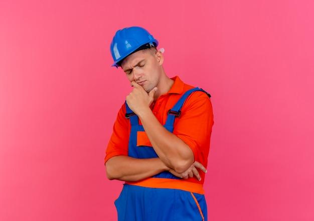 Avec les yeux fermés pensant jeune constructeur de sexe masculin portant l'uniforme et un casque de sécurité mettant la main sous le menton sur rose