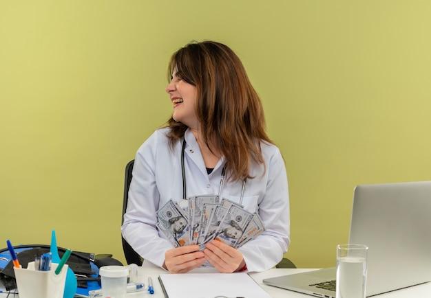 Avec les yeux fermés souriant femme médecin d'âge moyen portant une robe médicale avec stéthoscope assis au bureau de travail sur un ordinateur portable avec des outils nedical tenant de l'argent avec copie espace