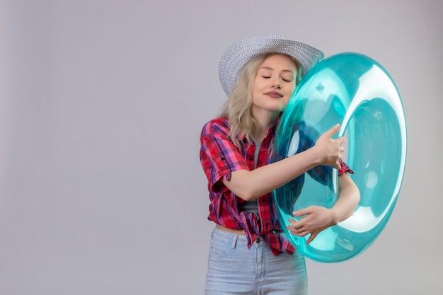 Avec les yeux fermés voyageur jeune fille portant une chemise rouge au chapeau haggé anneau gonflable sur fond blanc isolé