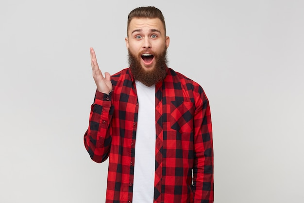 Les yeux ouverts, excité, surpris, beau jeune homme barbu en chemise à carreaux, bouche ouverte et main levée à cause de la stupéfaction, avec une coiffure fasion moustache, isolé sur fond blanc