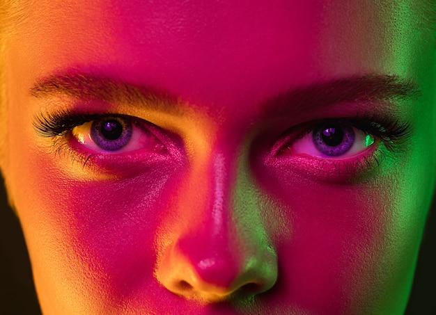 Yeux portrait de mannequin femme en néon sur fond de studio sombre