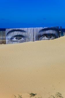 Yeux superposés sur les planches d'une dune de la plage de cortadura