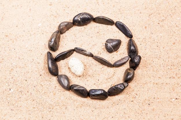 Yin yang dessiné avec des galets sur le sable d'une plage