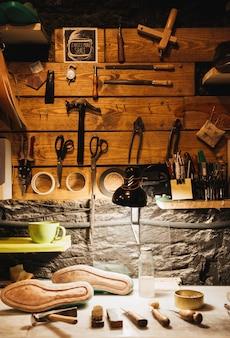 Ynstruments sur mur en bois à l'atelier de chaussures.