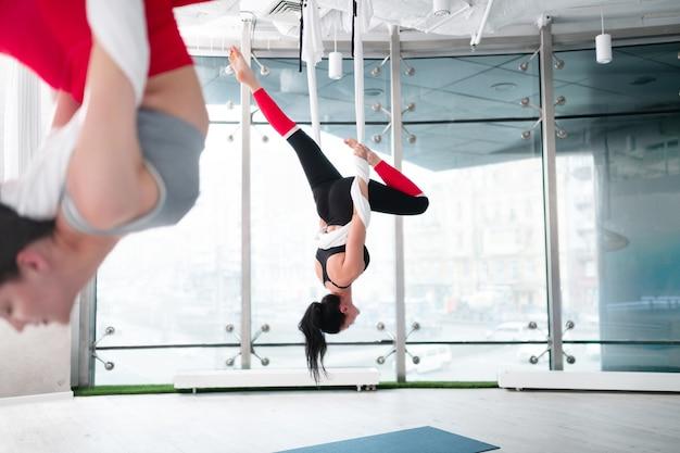 Yoga aérien ensemble. deux femmes en forme et minces portant des leggings confortables faisant du yoga aérien ensemble