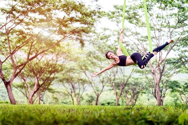 Yoga anti-gravité ou yoga aérien à l'extérieur avec un parc public