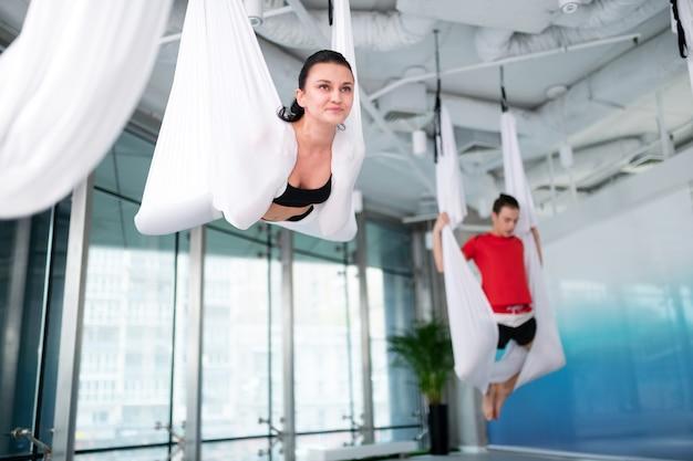 Yoga après le travail. femme brune se sentant motivée en assistant au yoga aérien après le travail