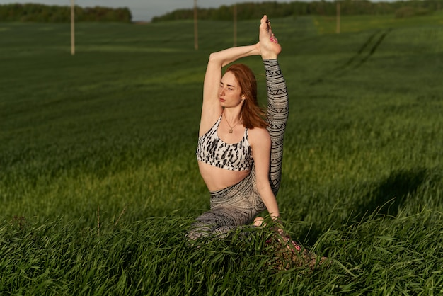Yoga au naturel. une femme rousse pratique le yoga en plein air. concept spirituel et émotionnel.