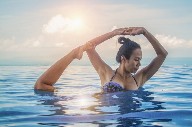 Yoga de belle femme dans la piscine bleu turquoise.