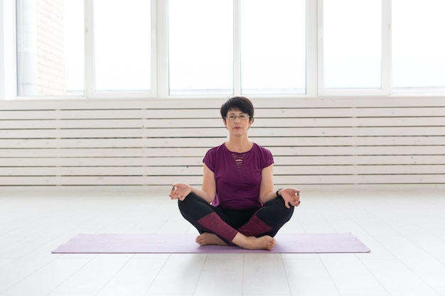 Yoga, concept de personnes - une femme d'âge moyen faisant du yoga dans la salle de sport