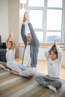 Yoga à domicile. père et ses enfants faisant du yoga ensemble à la maison et ayant l'air paisible