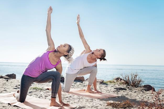 Yoga du matin. homme et femme mince et en forme faisant des exercices de yoga du matin ensemble près de la rivière