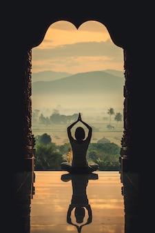 Yoga femme assise en lotus pose sur le temple pendant le lever du soleil, avec reflet dans le sol - effet de couleur de style vintage