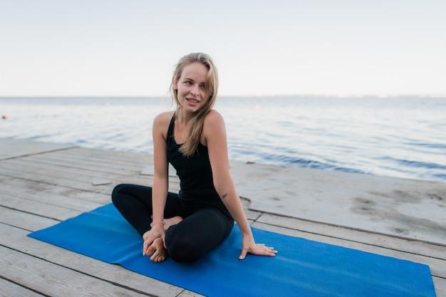 Yoga de la femme. détendez-vous dans la nature près du lac