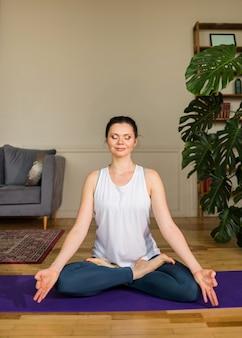 Yoga femme est assise les yeux fermés en position du lotus sur un tapis dans une pièce
