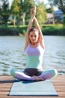 Yoga femme, se détendre dans la nature jeune fille faisant des exercices de fitness yoga en plein air dans un beau paysage.