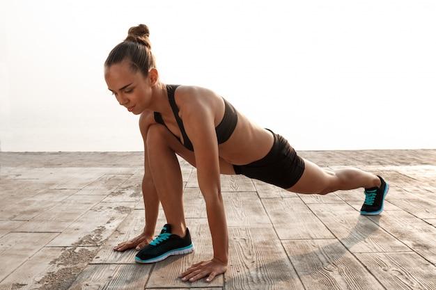 Yoga de formation jeune belle fille sportive au bord de mer.