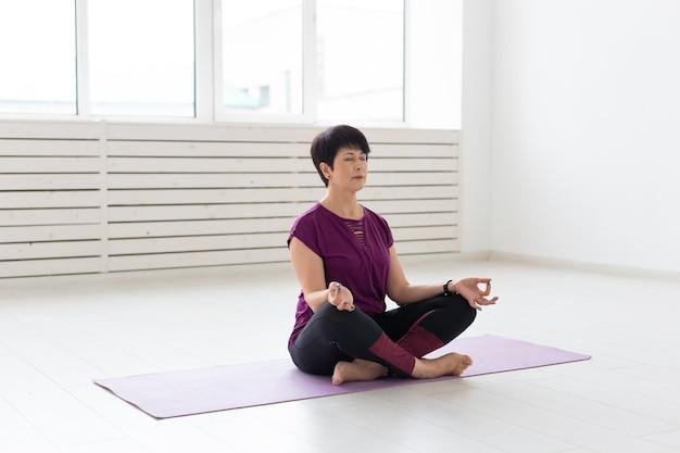 Yoga, harmonie, concept de personnes - femme d'âge moyen assise en position du lotus.