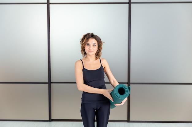 Yoga à l'intérieur. jeune femme en vêtements de sport prêt pour la gym et le yoga tenant un tapis vert.