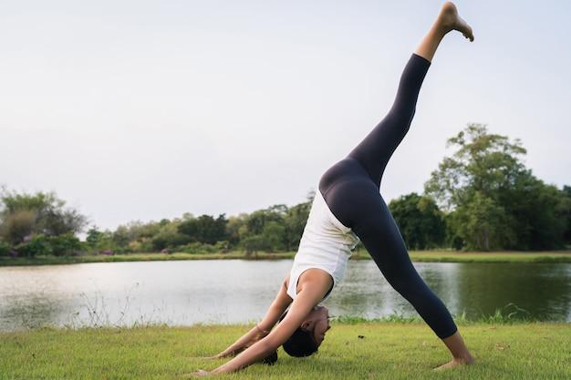 Yoga de jeune femme asiatique à l'extérieur garder son calme et médite tout en pratiquant le yoga