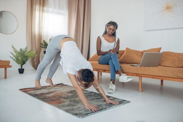 Yoga. jeune fille aux cheveux courts faisant du yoga et debout dans la pose de chien vers le bas