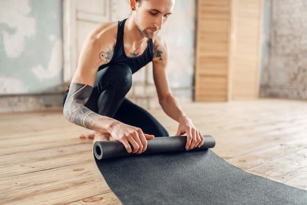 Yoga masculin avec tatouage sur place prépare le tapis pour la formation en salle de gym avec intérieur grunge.