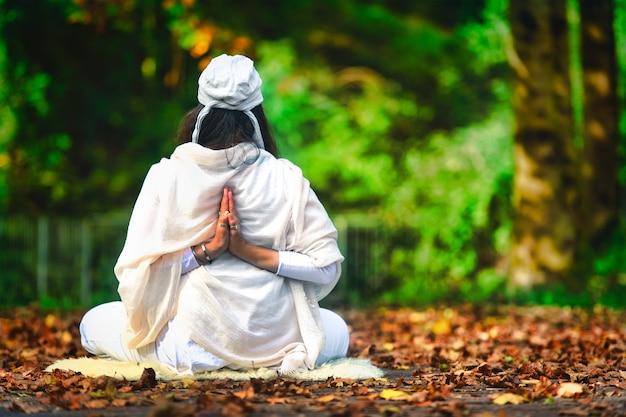 Yoga parmi les feuilles d'automne dans le parc