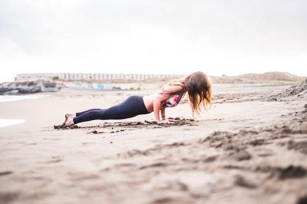 Le yoga et le pilates reposent sur une position forte pour résister et être dur. belle jeune femme faisant du fitness à la plage dans une activité de loisirs en plein air. sable et endroit solitaire au coucher du soleil. image lumineuse.