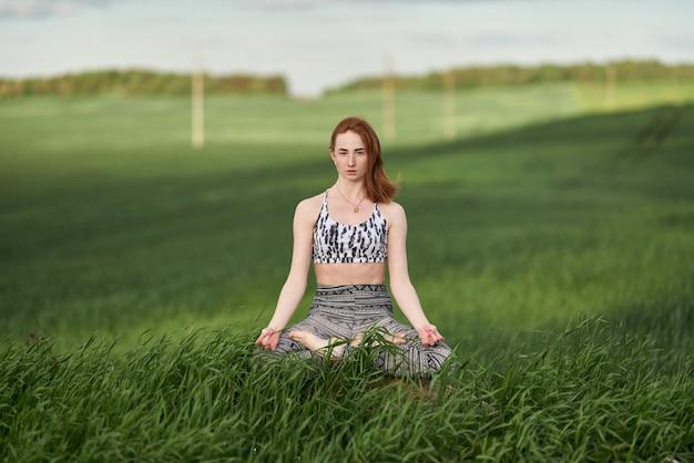 Yoga en plein air. femme heureuse, faire des exercices de yoga, méditer dans un parc ensoleillé. concept de mode de vie sain et de détente. jolie femme pratiquant le yoga sur l'herbe