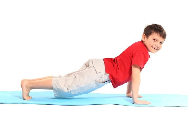 Yoga pour enfants. le petit garçon fait de l'exercice
