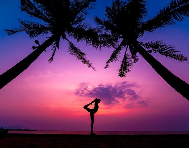 Yoga pratique belle jeune femme à la plage. exercice tôt le matin. lever du soleil