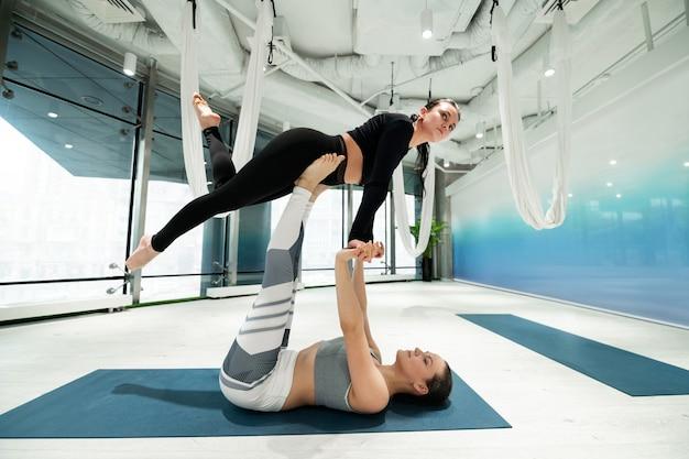 Yoga avec soeur. jeune femme portant des leggings noirs faisant du yoga fitness avec sa sœur aînée
