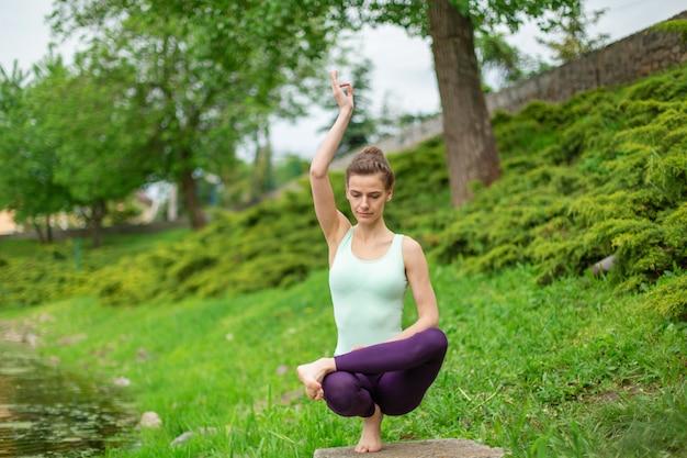 Yogi brune jeune et mince effectue des exercices de yoga complexes sur l'herbe verte.