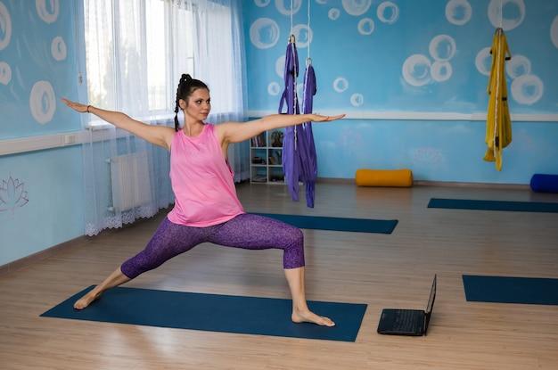 Une yogi exécute l'asana virabhadrasana à distance avec un ordinateur portable dans le hall