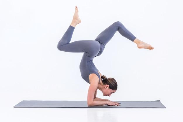 Yogi woman practicing yoga on mat sur fond blanc debout sur les coudes