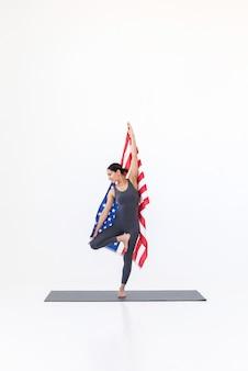 Yogi woman practicing yoga on mat sur fond blanc avec drapeau américain usa