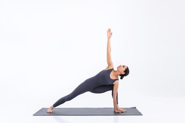 Yogi woman practicing yoga on mat on white scene in studio
