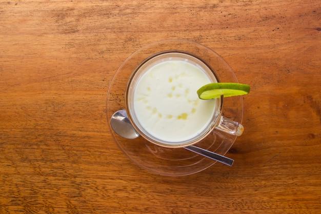 Yogourt au citron, lait frais dans un verre transparent posé sur une table en bois marron. vue de dessus.