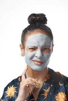 Yong drôle avec masque de beauté d'argile sur le modèle isolé de la peau