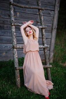 Yong élégante fille blonde à la robe rose sur l'escalier en bois de fond de jardin.