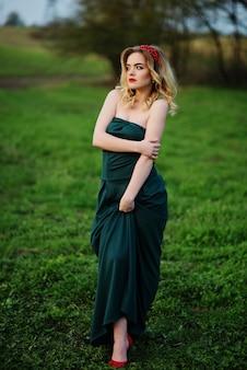 Yong élégante fille blonde à la robe verte sur le jardin au printemps.