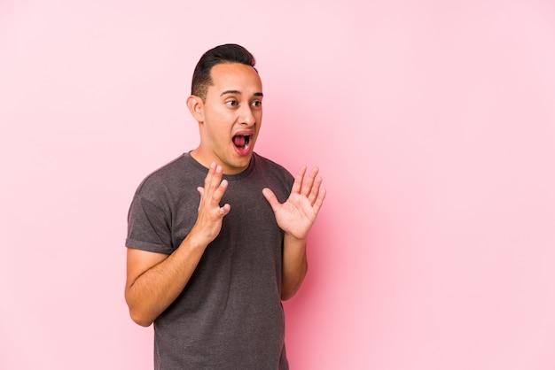 Yooung latin homme posant dans un mur rose crie fort, garde les yeux ouverts et les mains tendues.
