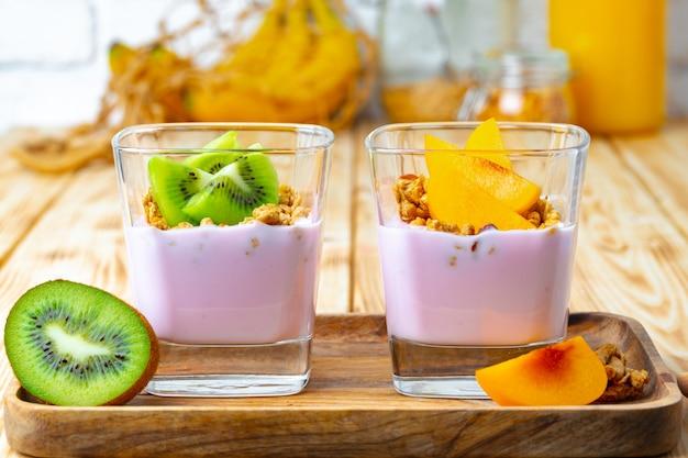 Youghurt aux petits fruits avec granola et fruits dans un verre