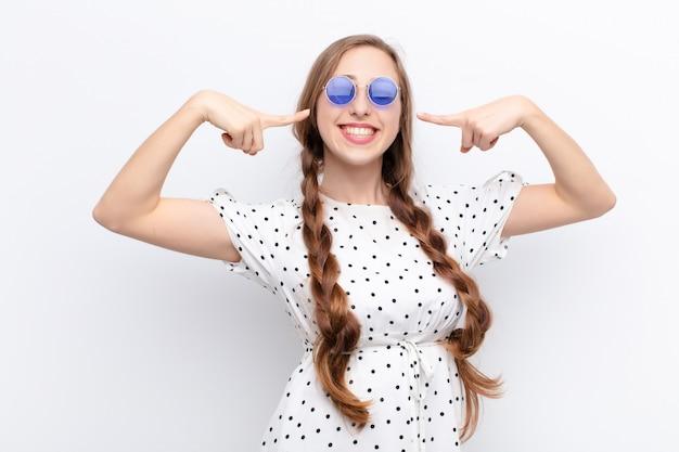 Yound blonde woman smiling pointant vers son propre large sourire, attitude positive, détendue et satisfaite sur le mur blanc