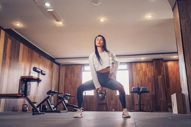 Young adult fitness woman doing swing exercice avec un kettlebell dans le cadre d'une séance d'entraînement de remise en forme