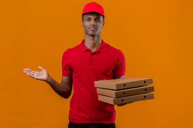 Young african american delivery man wearing red polo shirt and cap holding stack of pizza boxes looking confused and have dets over isolated orange